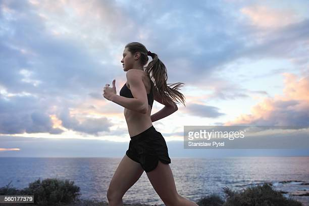Young woman running near ocean with cloudy sky