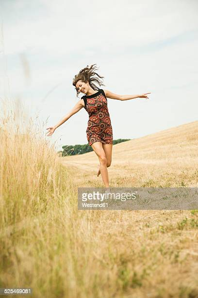 Young woman running on a harvested meadow