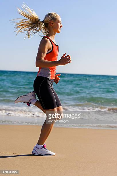 Young woman running on beach, Algarve, Portugal