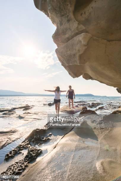 Joven corriendo en la playa con los brazos abiertos, abrazando la naturaleza