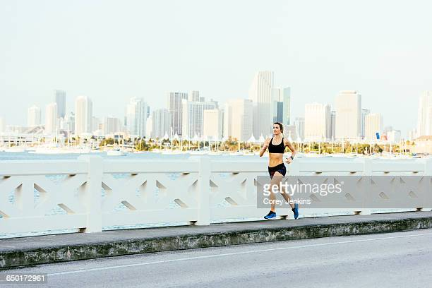 Young woman running on bridge pathway