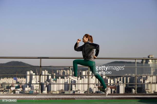 Young woman running on city rooftop