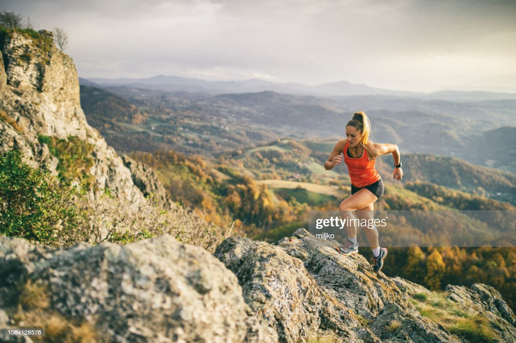 Young woman running on mountain : Stock Photo
