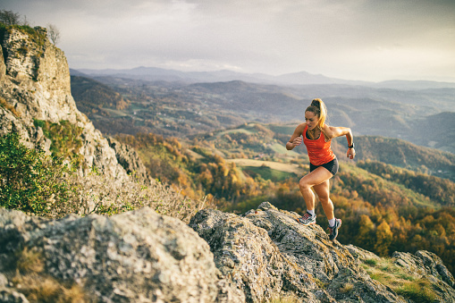 Young woman running on mountain 1064128576