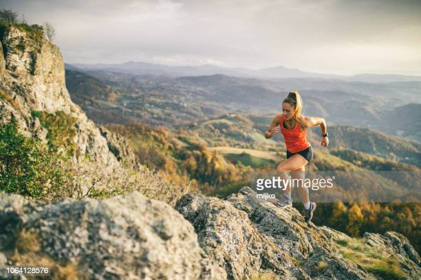 young woman running on mountain - atleta imagens e fotografias de stock