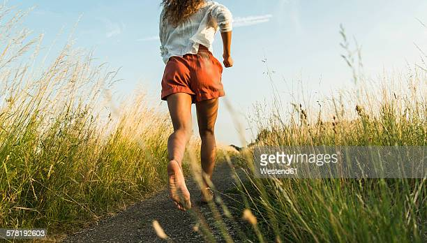young woman running on path in field - barfuß stock-fotos und bilder