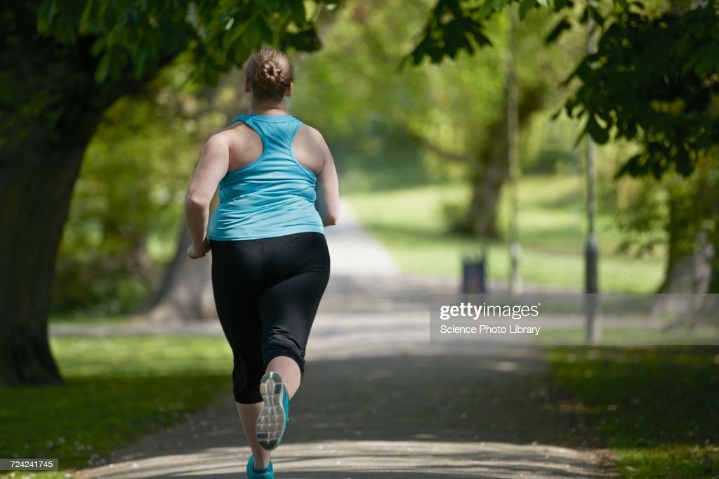 Young woman running on path, rear view : Stock Photo
