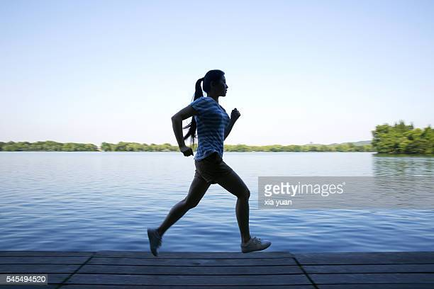 Young woman running on pier against lake