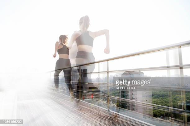 young woman running on rooftop - image photos et images de collection