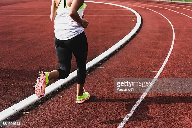 Young woman running on tartan track