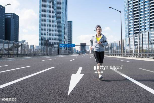 A young woman running on the road
