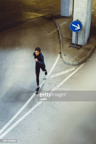 young woman running on the streets - center athlete stock pictures, royalty-free photos & images