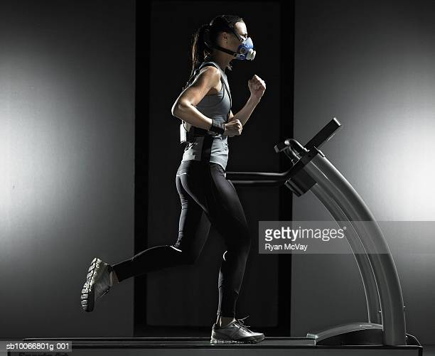Young woman running on treadmill, wearing oxygen mask, side view