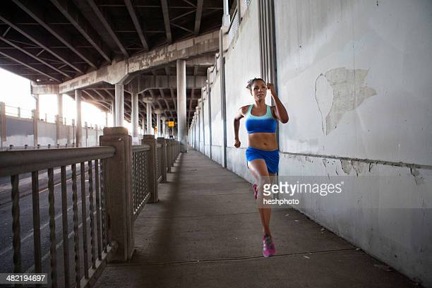 young woman running on urban bridge - heshphoto stock pictures, royalty-free photos & images