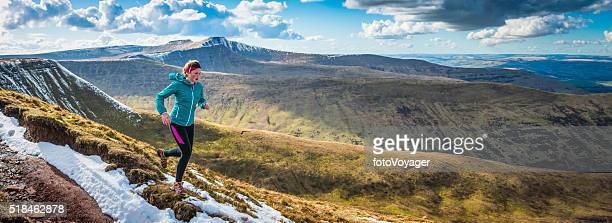 young woman running on wilderness trails on mountain ridge panorama - cross country running stock pictures, royalty-free photos & images
