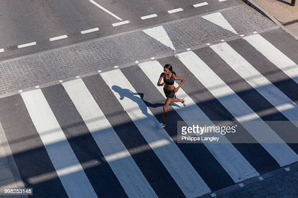 young woman running on zebra crossing - striped shirt stock pictures, royalty-free photos & images