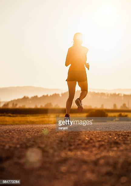 Young Woman Running Outdoors at Sunset