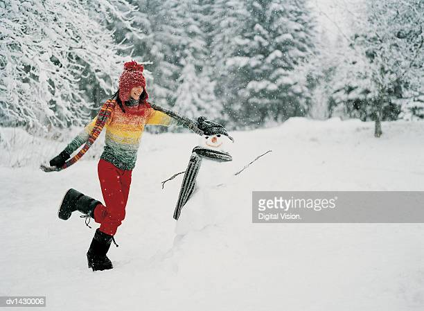 Young Woman Running Outdoors in the Snow Next to a Snowman