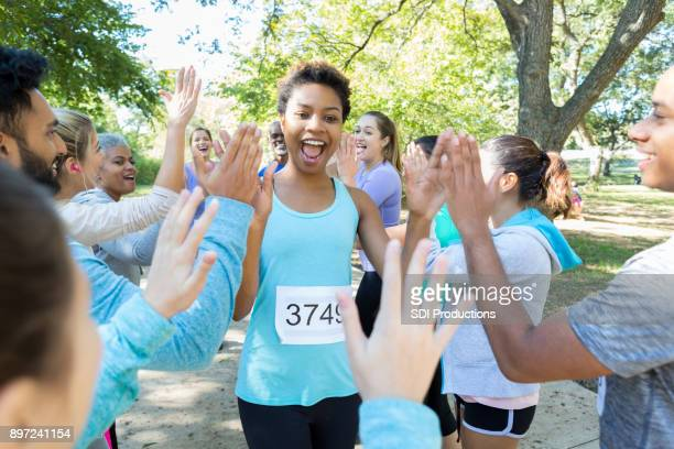 young woman running race is encouraged with high fives - charity benefit stock pictures, royalty-free photos & images