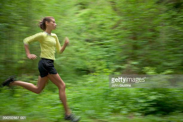 Young woman running, side view, trees in background (blurred motion)