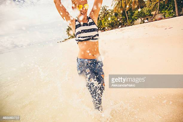 young woman running through the water - wet jeans stock photos and pictures