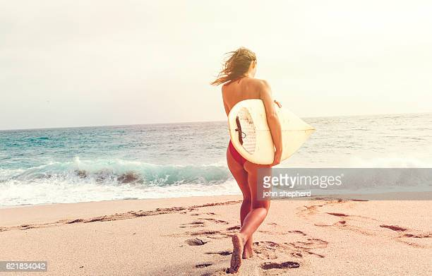 young woman running to the sea holding a surfboard.