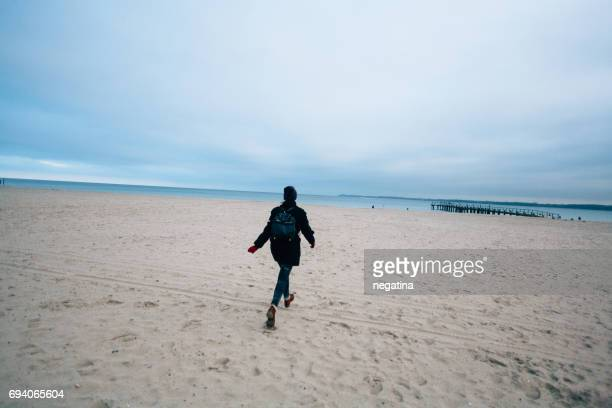 young woman running to the sea on the Travemuende beach in Germany