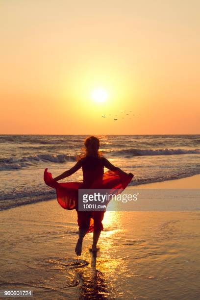 Young woman running to the sun at beach. Freedom concept. Elegance at sunset.