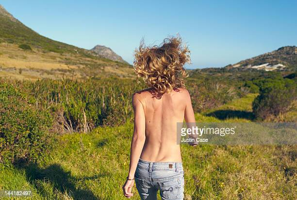 Young woman running topless in an open landscape