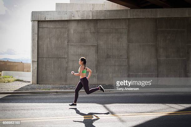 young woman running under freeway overpass - rennen stockfoto's en -beelden