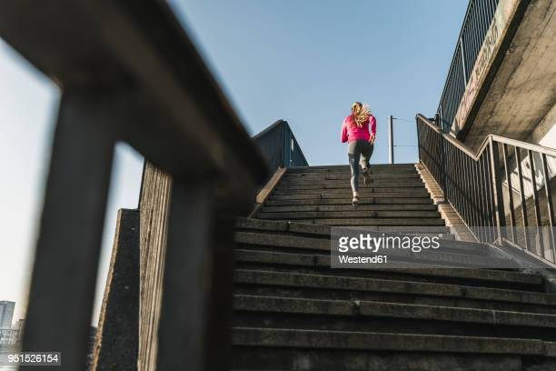 young woman running up stairs - sports training stock pictures, royalty-free photos & images