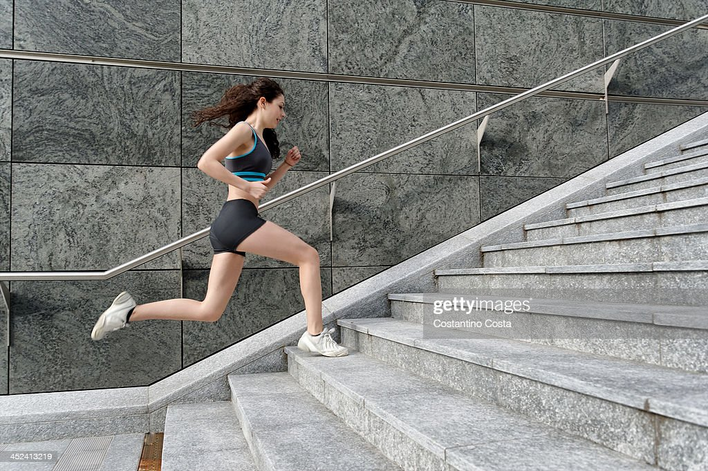 Young woman running up stairway : Stock Photo