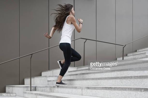 Young woman running up steps, low angle view
