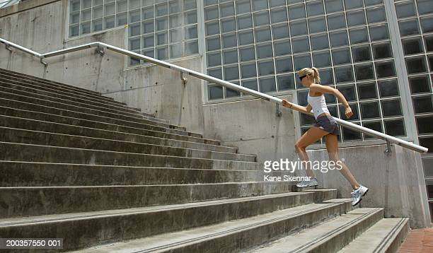 Young woman running up steps, side view