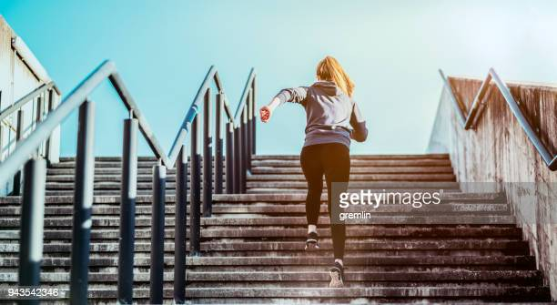 young woman running up the street concrete stairs - adversidade imagens e fotografias de stock