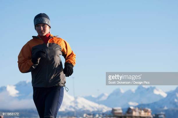 a young woman running with a snow covered mountain range in the background - home run ストックフォトと画像