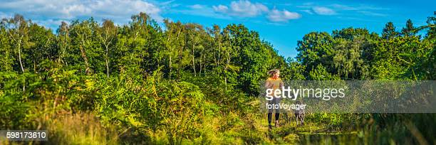 Young woman running with dog through green forest trail panorama