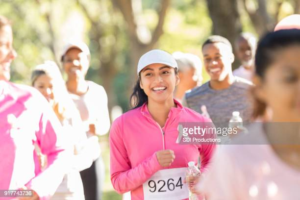 young woman running with fellow race for cure participants - charity benefit stock pictures, royalty-free photos & images