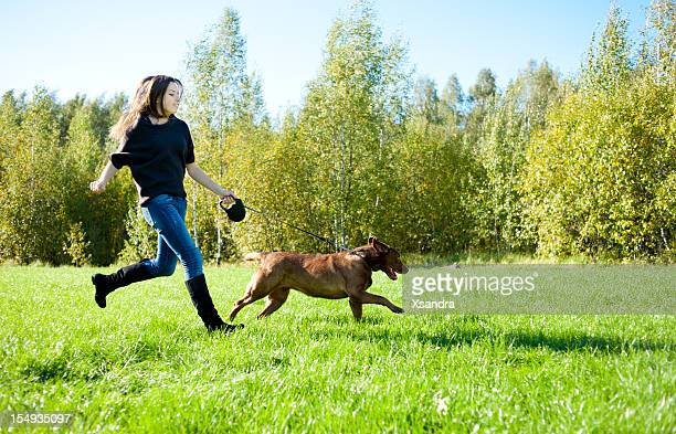 Young woman running with Labrador in grass