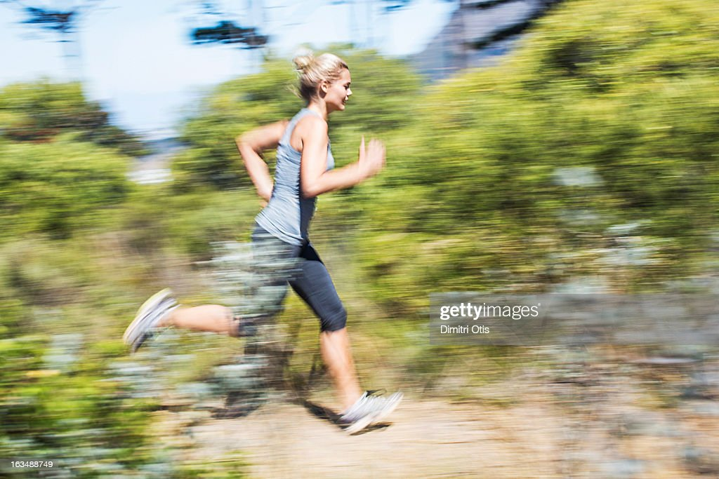 Young woman running with motion blur : Stock Photo