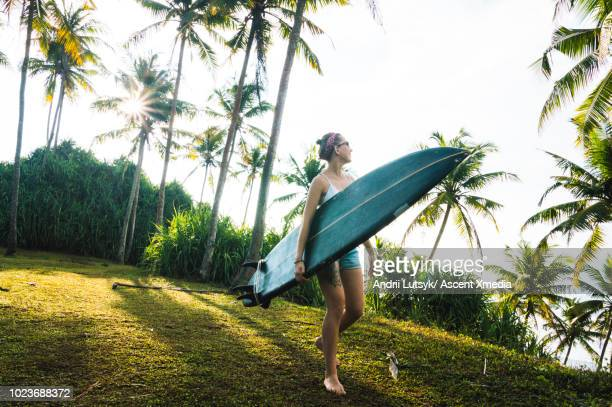 Young woman runs along beach with surfboard