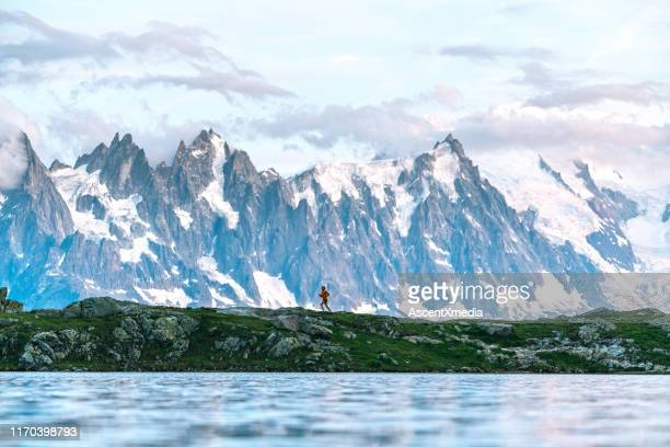 young woman runs along lake below mountains - auvergne rhône alpes stock pictures, royalty-free photos & images