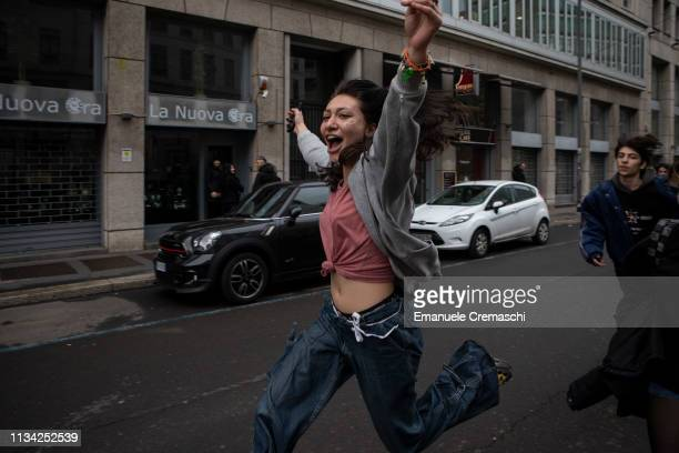 A young woman runs and jumps while she takes part in a student demonstration against gender violence and calling for gender parity on March 7 2019 in...