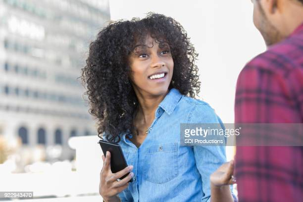 young woman runs into old friend on city street - stranger stock pictures, royalty-free photos & images