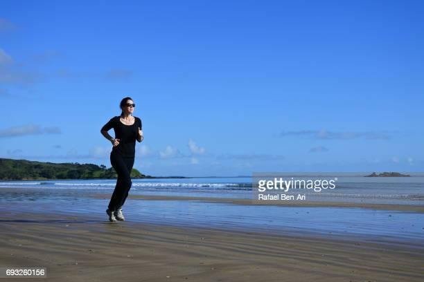 young woman runs on the beach - rafael ben ari stock-fotos und bilder