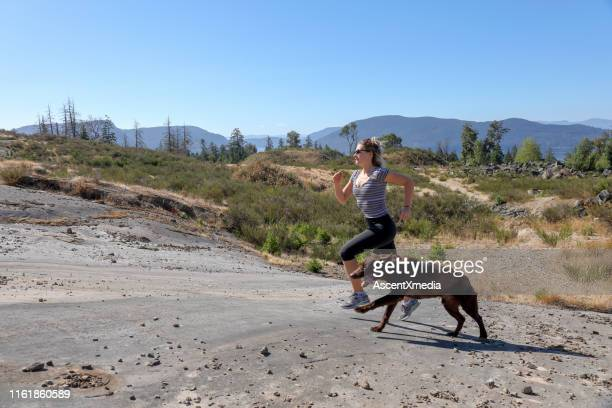 young woman runs through meadow with dog - self improvement stock pictures, royalty-free photos & images
