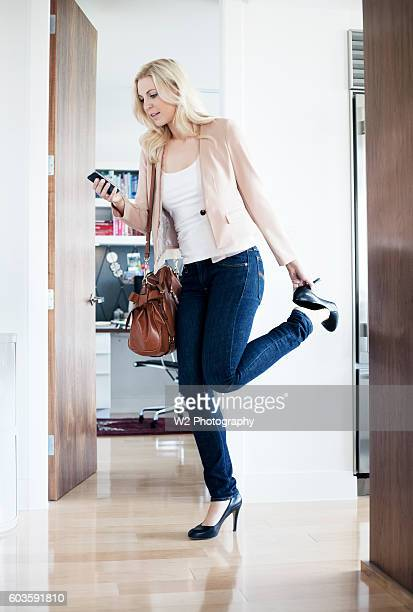 young woman rushing out of the house. - urgency stock pictures, royalty-free photos & images