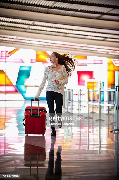 young woman rushing through the airport - woman hurry stockfoto's en -beelden