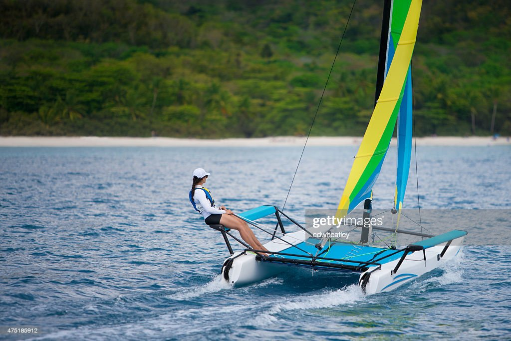 young woman sailing on a catamaran by the Caribbean beach : Stock Photo