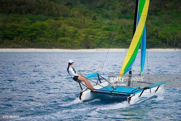 young woman sailing on a catamaran by the caribbean beach - catamaran stock photos and pictures